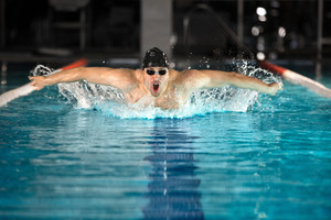 Young male swimmer swimming the butterfly stroke in a pool
