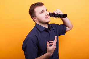 Young man acting silly talking on tv remote like is a phone. Young man being funny