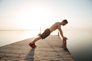 Young man athlete doing push-ups outdoors at the beach in the morning