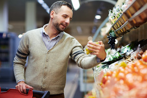 Young man choosing fruit in supermarket