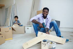 Young man drilling wooden planks while his son unpacking boxes on background