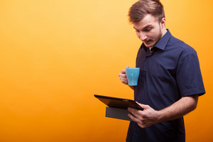Young man in blue shirt drinking coffee and keeping tablet in hand over yellow background. Smart man