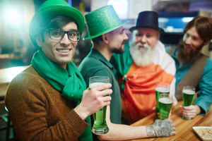 Young man in green hat and scarf holding Irish beer