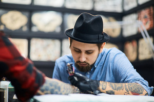 Young man in hat painting tattoo on arm of client
