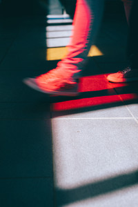 Young man in sneaker walking on the street. Bright light falling down through the colored glass windows on the floor. Cold colors and shadows on the floor