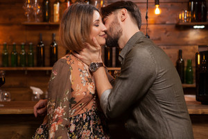 Young man kissing his fiance on a night out in a vintage pub. The young woman looks happy. Stylish couple in a warm lighten.