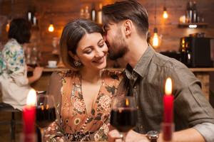 Young man kissing his fiance on a night out. The young woman looks happy. Stylish couple in a warm lighten restaurant.