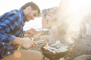 Young man roasting steaks on grill during picnic with friends at leisure