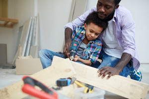Young man showing his son how to work with electric drill