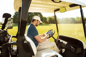 Young man sitting in a golf cart with a tablet computer