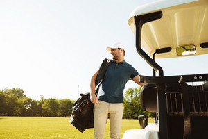 Young man standing with golf bag at the buggy car