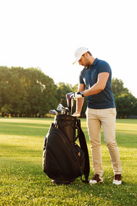 Young man taking out golf club from a bag while standing on field