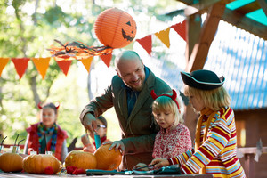 Young man talking to his daughters while cutting Halloween pumpkins