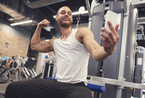 Young man tightening muscles over taking selfie