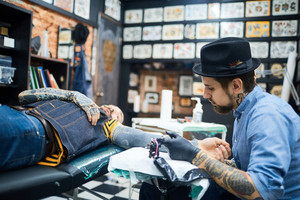 Young man visiting professional tattoo master