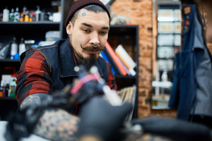 Young man visiting tattooer for making tattoo