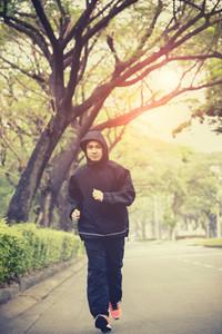 young man wearing hood jacket running on urban street