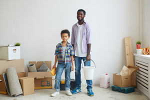 Young man with bucket and his son with sponge during housework