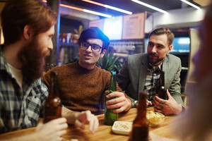 Young men having beer and talk in Irish pub
