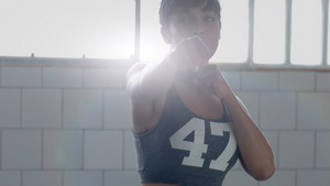 young mixed race african american woman makes a boxing workout in sunny loft Contour light looking throught the camera