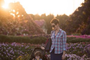 young mother and cute little girl in a baby stroller enjoying a beautiful day in the flower garden
