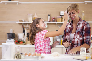 Young mother and her teenage daughhter playing with flour while making delicious food. Cheerful atmosphere.