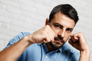 Young people, feelings and emotions. Portrait of white man looking at camera, ready to fight and boxing.