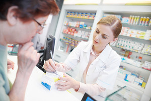 Young pharmacist helping elderly customer