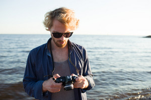 Young photographer with photocamera making photos of natural views by seaside