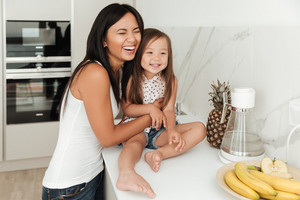 Young pretty asian woman and her daughter laughing while cooking on a kitchen at home