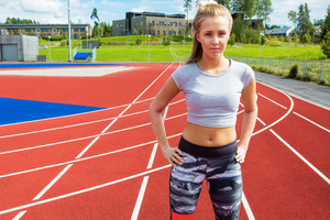 Young Runner Standing With Hands On Hips On Running Tracks