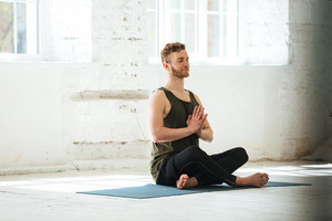 Young smiling guy with eyes closed sitting on a fitness mat and meditating in the gym