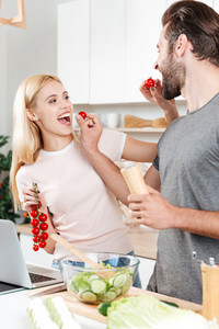 Young smiling man and woman at kitchen cooking with laptop and feeding each other