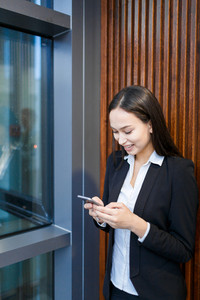 Young specialist with smartphone messaging at break in office