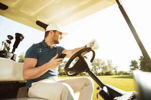 Young sportsman driving golf cart while using mobile phone