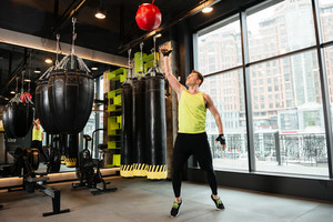 Young sportsman throwing weight ball while working out at the gym