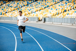 Young sprinter running on athletics track at the stadium