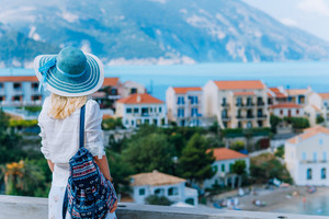 Young stylish traveler woman enjoying view of colorful tranquil Assos village. Female model wearing blue sunhat, white clothes and travel backpack enjoying her summer vacation in Kefalonia, Greece