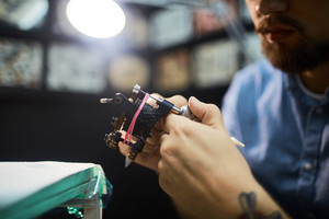 Young tattooist preparing tattoo-device for work