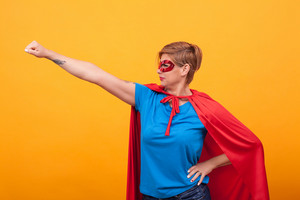Young woman dresed like superheros flying off to save the world over yellow background. Woman super powers.
