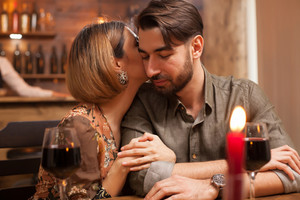 Young woman gently kissing the cheek of her boyfriend on a dinner date. Cozy restaurant ambiance. Candles burning