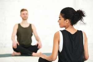 Young woman having a yoga class with male instructor in a studio