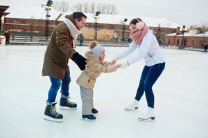 Young woman helping her daughter during skate on ice-rink