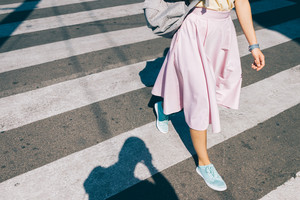 Young woman in a pink skirt and sneakers crossing the road in the summer