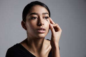 young woman in a profile portrait ccorrecting a makeup