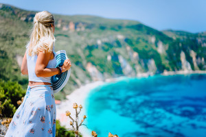 Young woman in front of Petani beach Kefalonia admiring highly excited picturesque panorama of emerald bay of Mediterranean sea and steep coastline island Greece