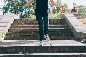 Young woman in jeans and sneakers, running down the stairs in the summer