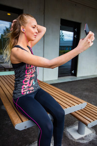 Young Woman In Sportswear Taking Selfie While Sitting On Bench