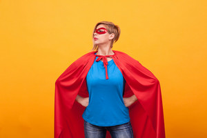 Young woman in superheros costume standing proudly over yellow background. Super powers. Red cape. red mask.