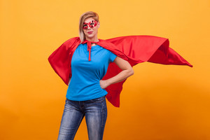 Young woman in superheros costume standing proudly with her red cape in the air over yellow background. Super powers.